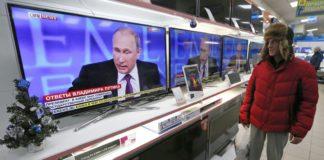 Путин на экране телевизора Фото: Reuters